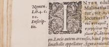 Printed rare book open to page with ornate initial letter